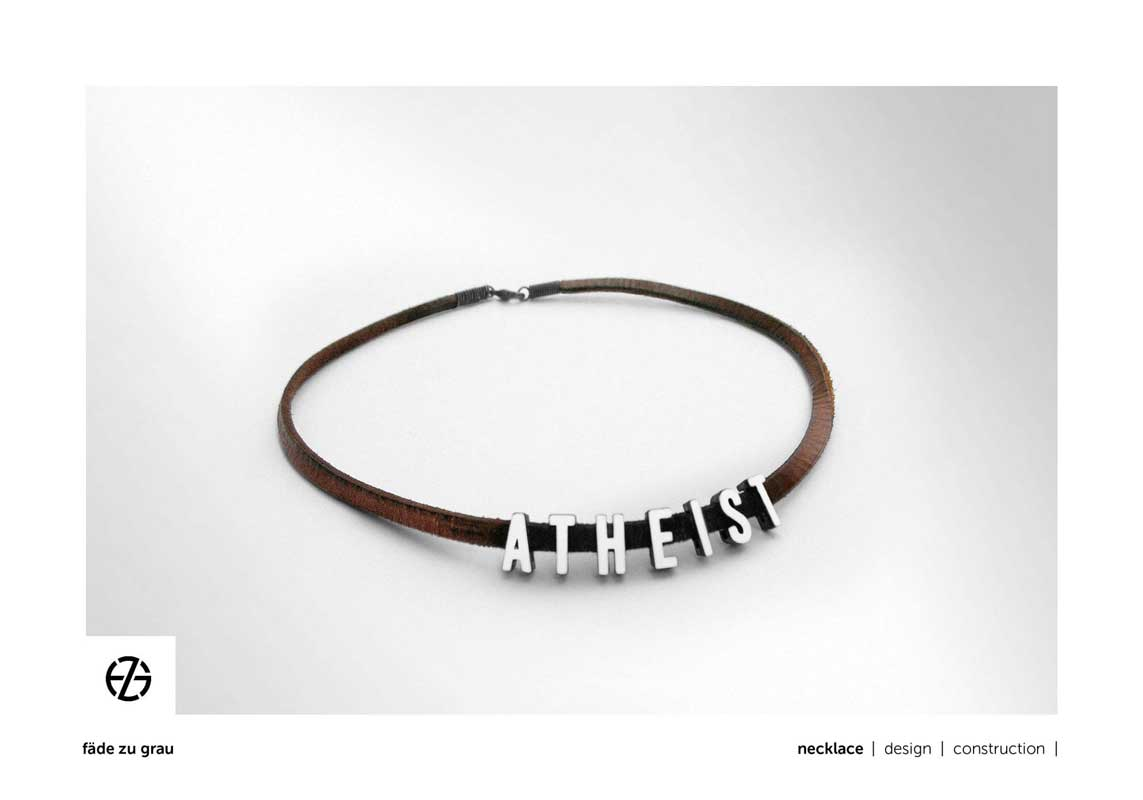 """brown leather band necklace with white painted metal letters spelling """"atheist"""""""