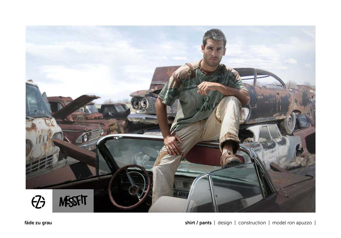 male fashion model in a junk yard presents green shirt and light brown pants