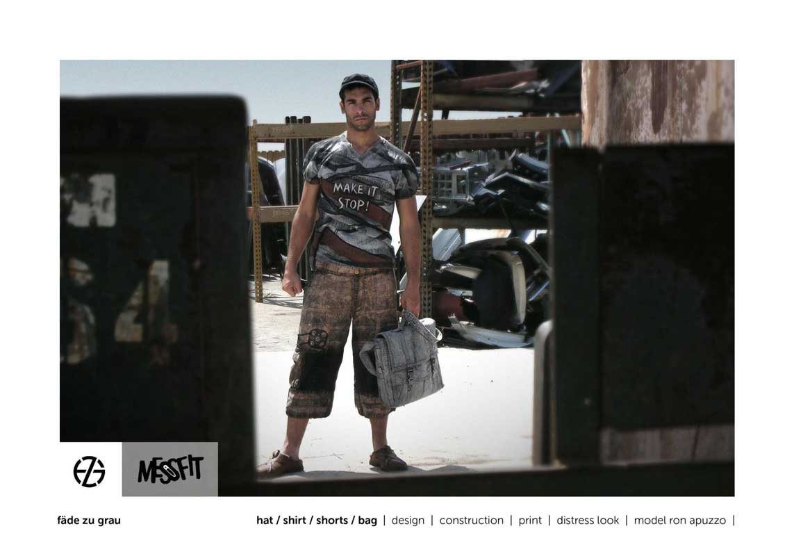 male fashion model in a junk yard presents gray t-shirt, brown shorts and a gray bag