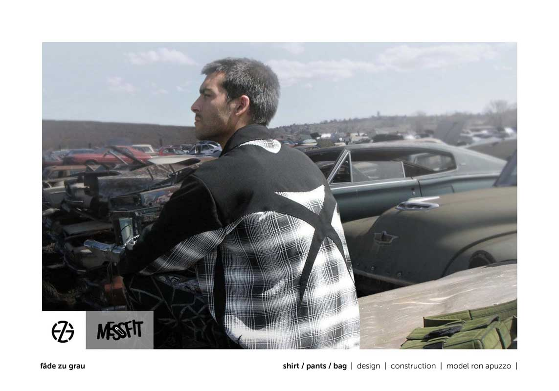 male fashion model in a junk yard presents black and white shirt with X on back