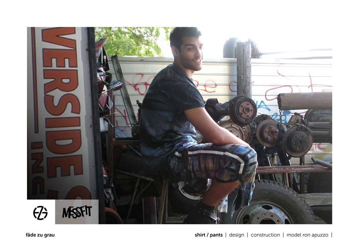 male fashion model in a junk yard presents blue t-shirt and blue jeans shorts, sitting
